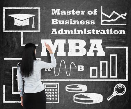business administration: Mujer de negocios que est� dibujando un diagrama de flujo sobre el t�tulo de MBA en el pizarr�n negro