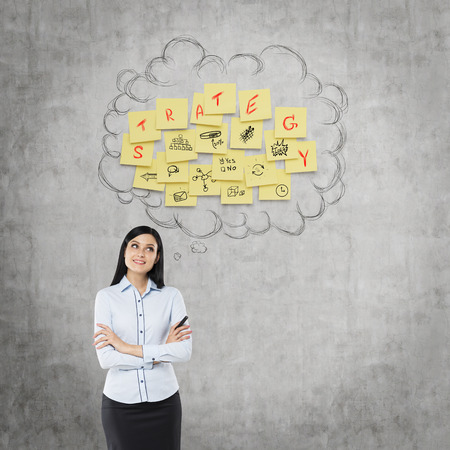 young businesswoman: Front view of the businessman who thinks about new business strategy. Yellow stickers are hanged as a cloud on the concrete wall.