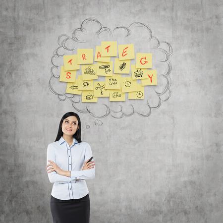 persona feliz: Vista frontal del hombre de negocios que piensa en la nueva estrategia de negocio. Pegatinas amarillas son ahorcados como una nube en la pared de hormigón.