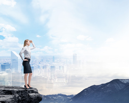 Business woman standing on a rock and looking at the flying business city. Illusion of the panoramic view of New York.