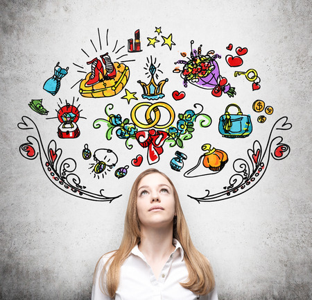 yearning: Young woman is dreaming about sopping. Colourful shopping icons are drawn on the wall. Concrete background. Stock Photo