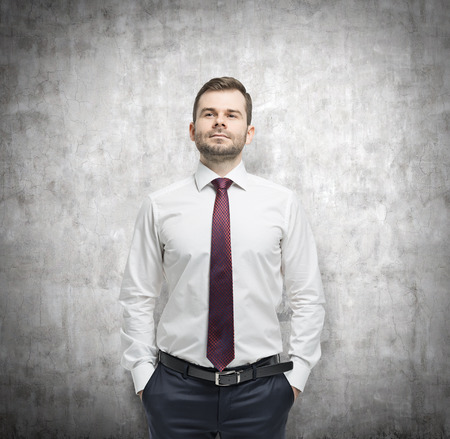 introspective: Confident businessman with hands in pockets. Concrete background.