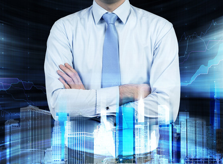 Close up of the businessman with crossed hands. Hologram cityscape on the front view and forex chart on background. Stock Photo