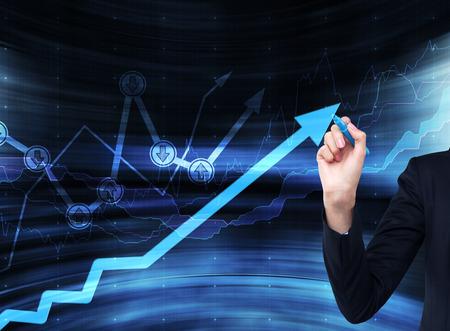 evolucion: Una mano está dibujando una flecha que crece en el pedregal de vidrio, de fondo azul oscuro con gráficos financieros.