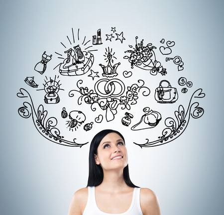 sopping: Young woman is dreaming about sopping. Shopping icons are flying in the air. Blue background.