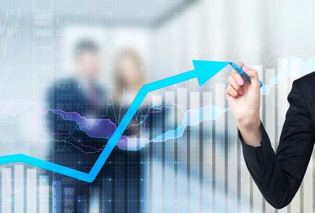 graficos de barras: Una mano est� dibujando una flecha que crece en el pedregal de vidrio, de fondo azul oscuro con gr�ficos financieros. Pareja de negocios en el desenfoque en el fondo.