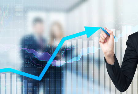 A hand is drawing a growing arrow on the glass scree, Blue dark background with financial graphs. Business couple in blur on the background. Archivio Fotografico