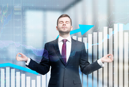 accounting: Meditative businessman is looking for the perfect business solution. Financial charts and office view in blur on the background. Stock Photo