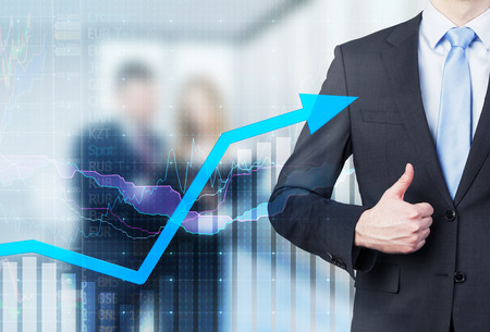 Businessman thumb up and growing arrow. Financial charts and business couple in blur on the background.