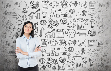 seeking solution: Young business woman is looking for the best solution for the business development process. Business icons are drawn over the concrete wall.