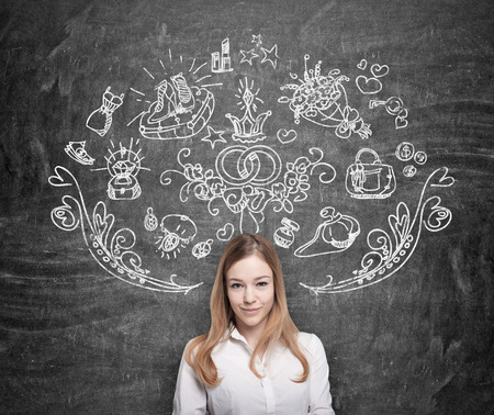 fulfilment: Young woman is dreaming about shopping. Shopping icons are drawn on the black chalkboard.