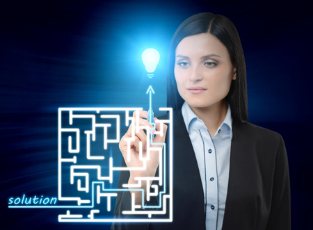 problems solutions: Brunette business woman is drawing a labyrinth with solution on the glass screen. Modern hologram illusion. Stock Photo