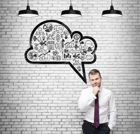 new strategy: Front view of the confident businessman, student, who is thinking about new business concepts. Drawn cloud with business icons on the white brick wall.