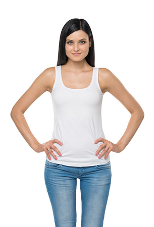 tank top: Brunette woman is in a white tank top and blue denims. Isolated.