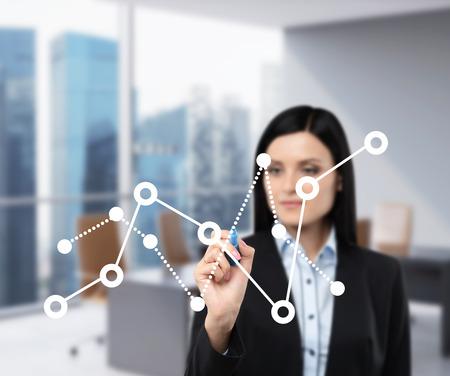 女性のビジネスは、ガラス スクリーン財務チャートの変動が描画されます。オフィス ビュー ビューでシンガポールにはバック グラウンドでぼかし