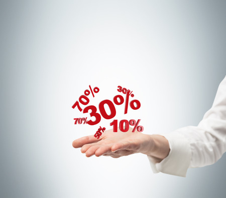 proportionate: A hand holds on the palm red discount signs. A concept of the big sale. Stock Photo