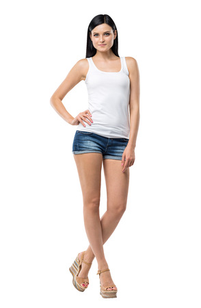 Full length portrait of a brunette woman who is in a white tank top and blue denim shorts. isolated.