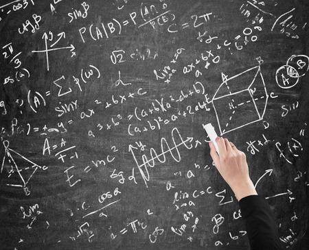 algebraic: A womans hand is writing math calculations on black chalk board. Analyst.