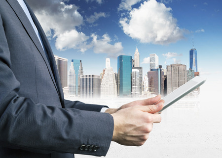 browses: Close-up of side view of a businessman who is browsing on his tablet. Sketch of New York cityscape. Stock Photo