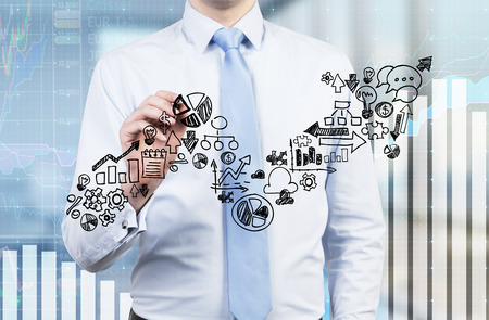 business performance: Businessman is drawing a growing arrow on the glass screen. Business icons as an integral part of the growing graph. Charts on the background. Stock Photo