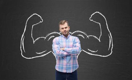 musculos: Hombre hermoso joven en camisa casual con las manos poderosas dibujados. Fondo de pizarra Negro.