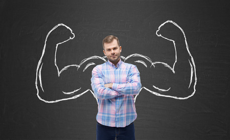 Young handsome man in casual shirt with drawn powerful hands. Black chalkboard background. Stockfoto