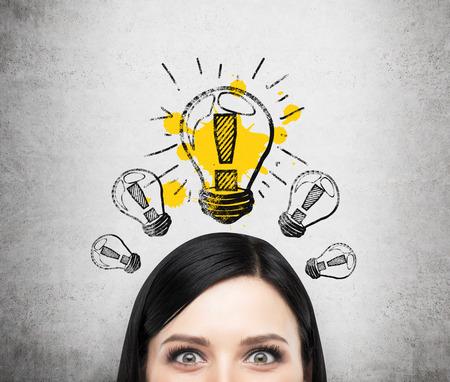 Ein Kopf der jungen brunette Dame, die über neue Geschäftsideen zu denken ist. Eine Glühbirne auf der Betonwand gezogen.