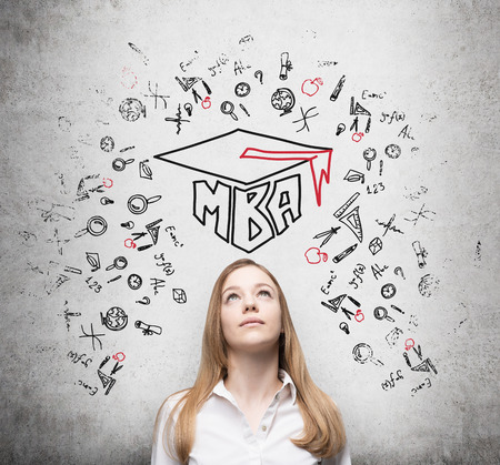 master degree: Young lady is thinking about MBA degree. Drawn a graduation hat and the range of educational icons on the concrete background . Stock Photo