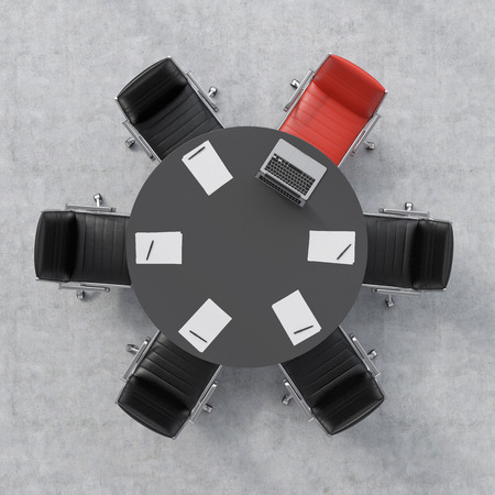 round chairs: Top view of a conference room. A black round table, six chairs, one of them is red. A laptop and five papers. Office interior. 3D rendering. Stock Photo