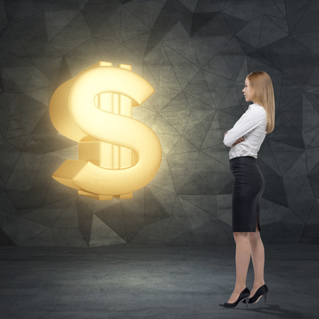 avarice: Side view of young business lady who is looking at the huge golden dollar sign. Contemporary background. Stock Photo