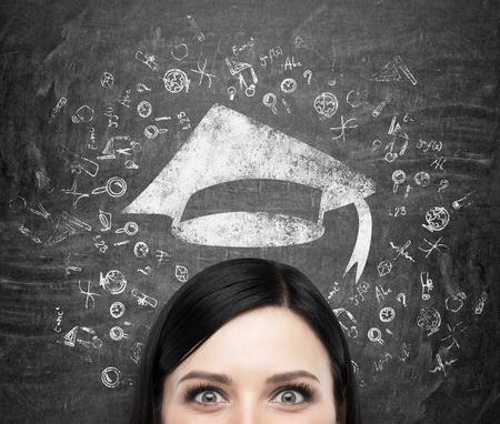 graduacion: A la cabeza de la señora joven morena que está pensando en la educación universitaria. Iconos educativos dibujado y un sombrero de graduación en el fondo de pizarra negro.