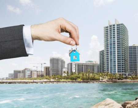A hand is holding a key from the new home. A concept of real estate property agency. Miami cityscape on the background.