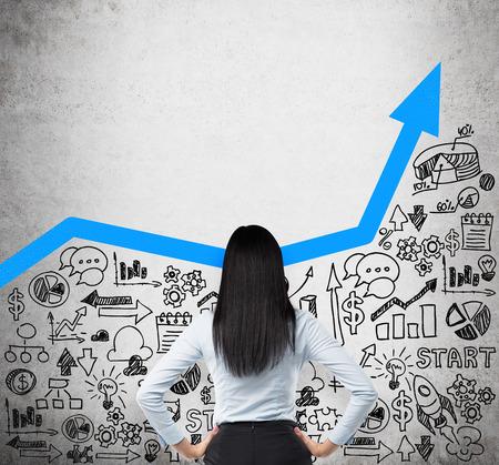 Vista posterior de la dama de negocio que está buscando a las nuevas ideas de negocio. Azul flecha creciente como concepto de negocio de éxito. Iconos de negocio se dibujan en el muro de hormigón.