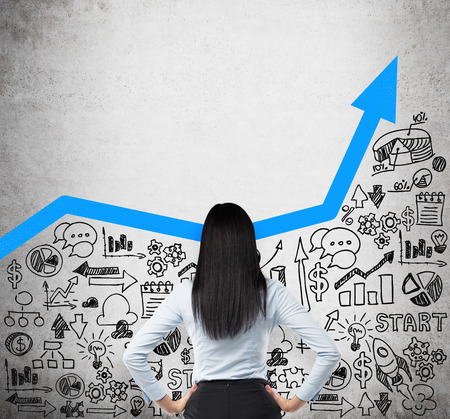 incremento: Vista posterior de la dama de negocio que está buscando a las nuevas ideas de negocio. Azul flecha creciente como concepto de negocio de éxito. Iconos de negocio se dibujan en el muro de hormigón.