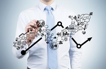 planeaci�n: Hombre de negocios est� drenando una flecha que crece en la pantalla de vidrio. Iconos de negocio como una parte integral de la gr�fica de crecimiento.