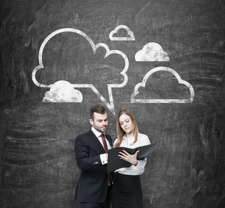 clouding: Double checking of the essential information about business project. A couple in formal clothes are holding the black document folder. Data clouds are drawn on the wall behind them. Black chalkboard.