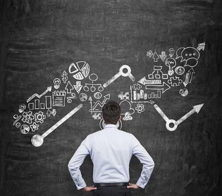 유행: 사업 기회에 대해 생각하는 사업가의 후면보기. 중요한 부분으로 화살표와 비즈니스 아이콘을 성장. 배경으로 검은 칠판. 스톡 콘텐츠