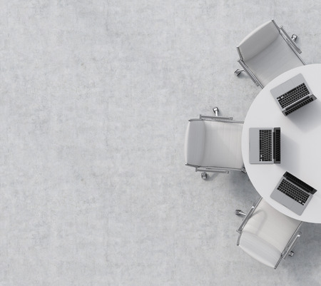 Vista dall'alto di una metà della sala conferenze. Una tavola rotonda bianca, tre sedie in pelle bianca. Tre computer portatili sono sul tavolo. ufficio interno. il rendering 3D.