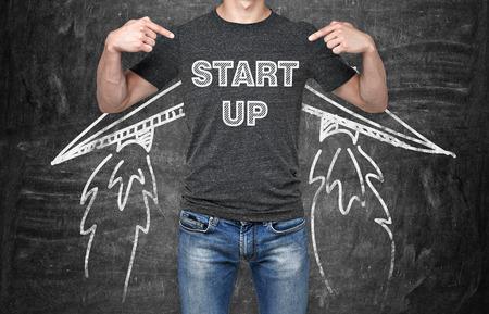 Een zakenman is te wijzen op in de borst waar is een woord collocatie 'start-up'. Een concept van het opstarten van nieuwe business. Drawn vleugels. Zwart krijt boord op de achtergrond. Stockfoto