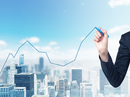 A hand is drawing a growing line graph on the glass screen. New York City space on the background. Stock Photo - 43982069