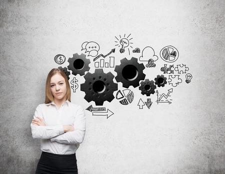 Une jeune femme d'affaires avec les mains croisées. Gears sont dessinés sur le mur de béton. Un concept de processus d'optimisation des affaires.