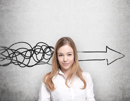 mujer pensando: Joven y bella mujer est� pensando en concepto de desarrollo de negocios. Un enorme flecha se dibuja en la pared de hormig�n. Foto de archivo