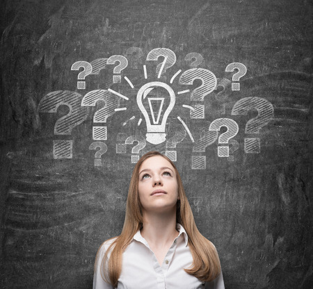 Beautiful young woman is thinking about undiscovered issues. Question marks and a light bulb are drawn on the black chalkboard behind the person.