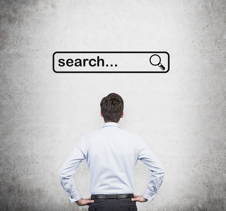 searchbar: Rear view of the man in the shirt who is looking at the browsing line. A concept of searching some information in the Internet. Stock Photo