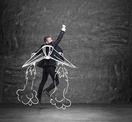 launching: A concept of business angel. A businessman is flying over the black chalkboard.