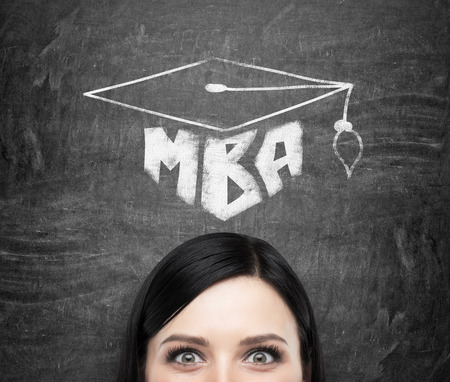 master degree: A head of young brunette lady who is thinking about MBA degree. Drawn a graduation hat on the black chalkboard background . Stock Photo
