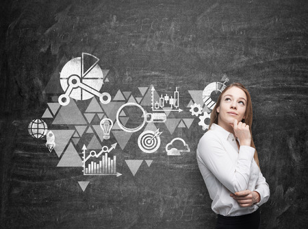 black board: Young business woman is thinking about business optimisation scheme. Black chalk board as a wall on the background.