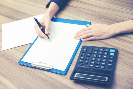 personal data assistant: Closeup of a business womans hands while writing down some essential quantitative information. Calculating machine, paper and a pen. Toning filter. Stock Photo