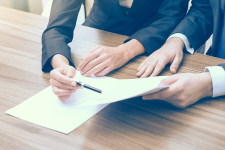 solving: Double checking of the essential information about business project. A couple in formal clothes are looking at the documents. Toning filter. Stock Photo