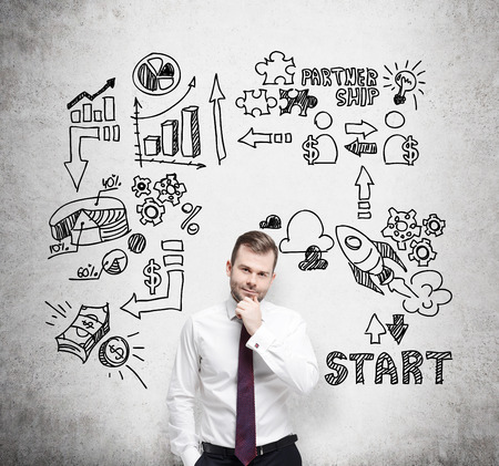 commencing: Confident businessman is thinking about business opportunities. A concept of brainstorm. Business icons are drawn behind the person on the concrete wall. Stock Photo